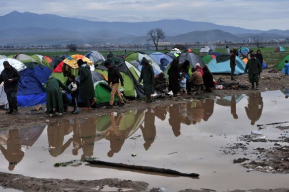 People are reflected in a puddle of rainwater near tents set up at the Greek-Macedonian border near the Greek village of Idomeni, where thousands of refugees and migrants are trapped by the Balkan border blockade, on March 9, 2016. The main migrant trail from Greece to northern Europe was blocked on March 9 after western Balkan nations slammed shut their borders, hiking pressure for an EU-Turkey deal and exacerbating a dire situation on the Macedonian border. / AFP / SAKIS MITROLIDIS